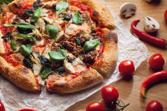 Fresh pizza with ingredients on wooden table Stock Photo