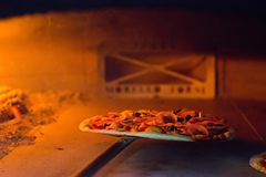 Fresh pizza inside the oven cooking for few minutes. Royalty Free Stock Photos