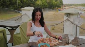 Fresh pizza on the table, a woman is preparing to eat it. Fresh pizza on the table, a woman is preparing to eat it stock video footage