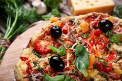 Fresh pizza with tomatoes, cheese and mushrooms on wooden table closeup Royalty Free Stock Image