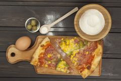 Fresh pizza on a wooden cutting board. Stock Photo