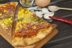 Fresh pizza on a wooden cutting board. Stock Image