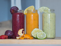Fresh plum, banana, spinach and orange drinks on wooden table. Fresh raspberry, banana, spinach and orange drinks on wooden table. Detox diet concept Royalty Free Stock Photos