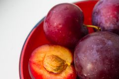 Fresh plum fruit in the red saucer on white background Royalty Free Stock Image