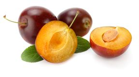 Fresh plum fruit with green leaf and cut plum slices isolated on white background royalty free stock photography