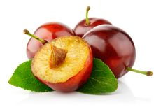 Fresh plum fruits with green leaves Royalty Free Stock Images
