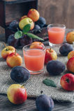Fresh plum juice. The juice in the glass is surrounded by plums and apples on a wooden table. Still Life with Plums Stock Photo