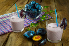 Fresh plum prune healthy drink. Fruit drink, plum smoothies, prune yogurt, diet healthy drink in a glass on a dark wooden background, horizontal. Selective focus Stock Images