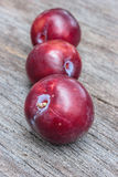 Fresh plum in a row on wooden background. Stock Photography