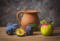 Fresh plums, apples and a ceramic carafe Royalty Free Stock Photos