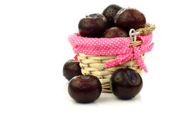 Fresh plums in and around a wicker basket Stock Photos