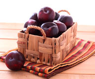 Fresh plums in the basket. On the napkin Stock Photos