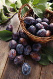 Fresh plums in basket on brown wooden background Stock Photo