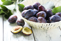 Fresh plums in basket on white wooden background Royalty Free Stock Photos
