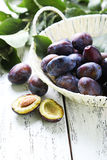 Fresh plums in basket on white wooden background Stock Image