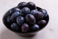 Fresh plums in black bowl. Fresh organic tasty plums in black bowl Stock Images