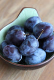 Fresh plums in a bowl. Fresh ripe plums in green bowl. Selective focus Stock Images