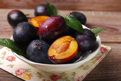 Fresh plums in bowl on wooden background Stock Photos