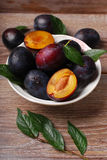 Fresh plums in bowl on wooden background Stock Images