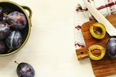 Fresh plums in bowl on wooden table. Royalty Free Stock Photography