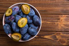 Fresh plums in bowl on wooden table stock photography