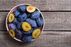 Fresh plums in bowl on wooden table Fruit background. Fresh plums in bowl on wooden table . Fruit background royalty free stock image
