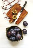 Fresh plums in bowl on wooden table. Top view Stock Image