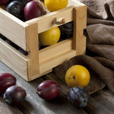 Fresh plums in box on wooden board Royalty Free Stock Images