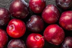 Fresh plums on dark stone background, macro. Healthy summer fruits. Top view stock photos