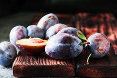 Fresh plums on dark wooden background Stock Photo