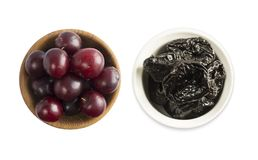 Fresh plums and dried prunes isolated on a white background. Dried prunes and fresh plums in a bowl on white background. Dried pru. Nes and plums with copy space Stock Image