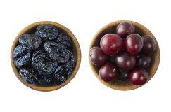Fresh plums and dried prunes isolated on a white background. Dried prunes and fresh plums in a bowl on white background. Dried pru. Nes and plums with copy space Stock Photography