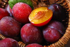 Fresh plums falling out of a basket Stock Image