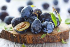 Fresh plums with leaves. On wooden background stock photo