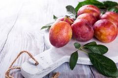 Fresh plums on marble cutting board Royalty Free Stock Images