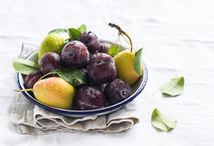 Fresh plums and pears on a white enamel plate Stock Photo