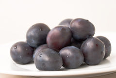 Fresh plums on the plate Royalty Free Stock Photo