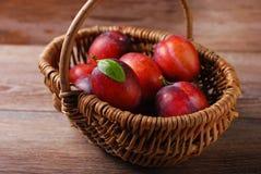 Fresh plums in a wicker basket Stock Photo