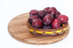 Fresh plums in the wooden basket Royalty Free Stock Photos