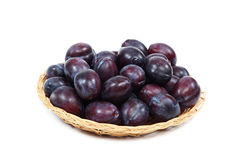Fresh plums in a wooden basket on white background. Stock Image