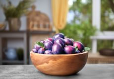 Fresh plums in wooden bowl. On table Stock Photography