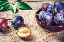 Fresh plums on wooden table. Blue and violet plums on wooden table Royalty Free Stock Photos