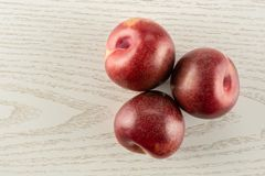 Fresh pluot interspecific plums on grey wood royalty free stock photography