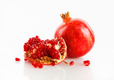 Fresh pomegranate fruit. Ripe tasty fresh red pomegranate fruit and its grain with reflection on a light background. Studio shot Royalty Free Stock Photo