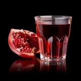 Fresh Pomegranate Juice. A view of a halved pomegranate with a fresh juice in the glass near it, on a black background Royalty Free Stock Image