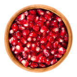 Fresh pomegranate seeds in wooden bowl over white Stock Images
