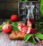 Fresh pomegranates and juice, selective focus. Fresh pomegranates and juice on a wooden table, selective focus Royalty Free Stock Images