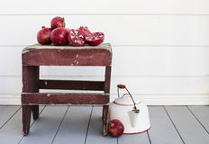 Fresh pomegranates on weathered table on porch with tea pot. Freshly picked pomegranates displayed on a small weathered table.  An old white with red trim tea Stock Photo