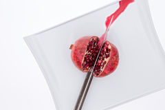 Fresh pomegrate being cut in half with a knife Stock Images