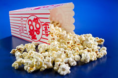 Fresh Popcorn. A spilled box of freshly popped popcorn against a blue background Stock Images